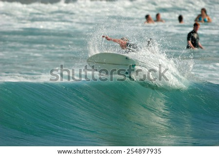 A surfer executes a radical move as seen from behind on a beautiful, blue wave in the ocean. - stock photo