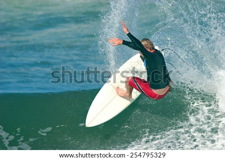 A surfer executes a radical move on a smooth, blue ocean wave. - stock photo