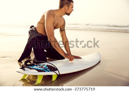 A surfer getting ready for the surf - stock photo