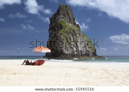 A surfer is laying under an umbrella waiting for waves. The deserted beach is shot against deep blue skies with few clouds and a huge rock in the middle. The picture is taken on Fernando de Noronha - stock photo