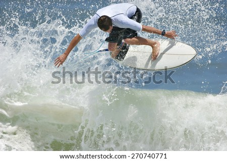 A surfer launches a radical backhand aerial on a wave.