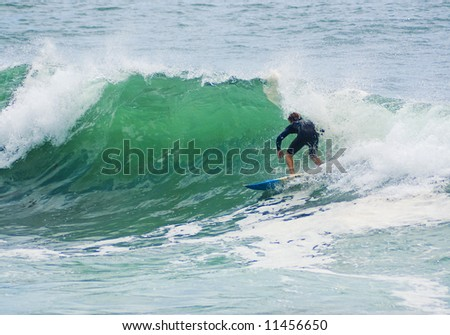 a surfer leans into a surf wave as it starts to break