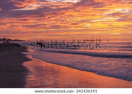A surfer on shore silhouetted against a brilliantly colored sunset on Playa Tamarindo, Guanacaste, Costa Rica - stock photo