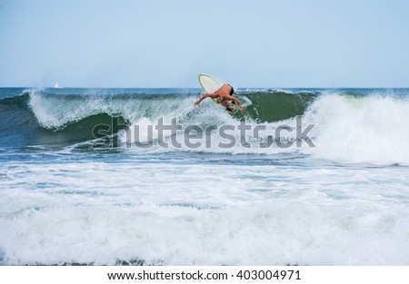 A surfer rides the wave along coast in Spring Lake New Jersey. - stock photo