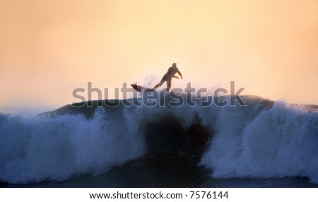 A surfer riding a big wave at sunset - stock photo