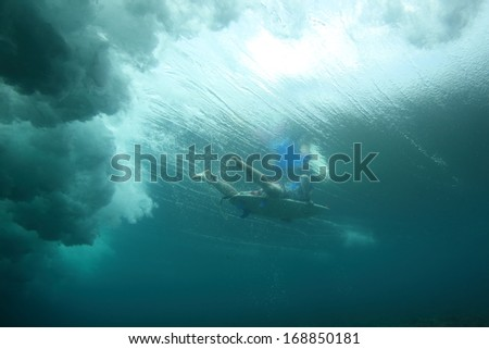 A surfer safely duck dives under a wave in Fiji - stock photo