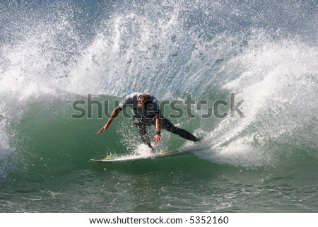 A surfer slashes a turn on a left hand wave.