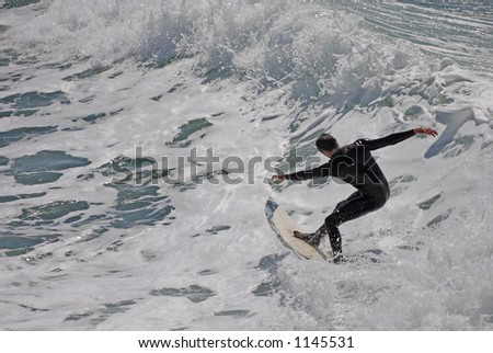 A surfer slices back on a wave near Pismo Beach, CA. - stock photo