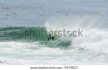 a surfer surfing out of a big wave about to dump him - stock photo