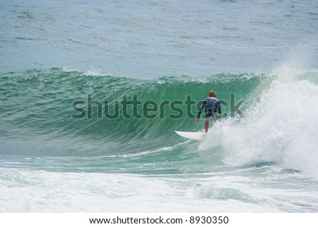 a surfer surfs along the face of a large powerful wave on the ocean - stock photo