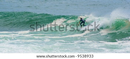 a surfer surfs along the face of a large powerful wave on the ocean trailing hand in the ocean