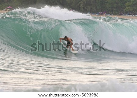 A surfer tucks into a hollow wave and attempts to get barreled