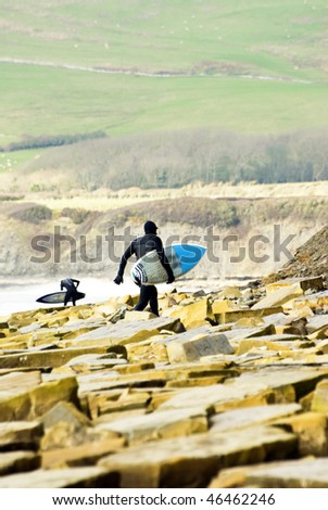 A surfer walking across a rocky coastline with beautiful green hills in the backround - stock photo