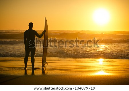 A surfer watching the waves at sunset in Portugal. - stock photo