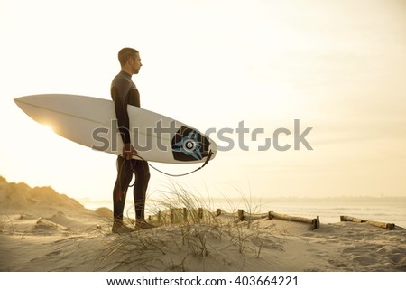 A surfer with his surfboard at the dunes looking to the waves - stock photo