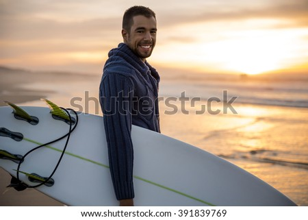 A surfer with his surfboard at the sunset looking to the waves - stock photo