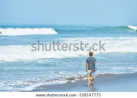 A surfer with his surfboard go  to the waves