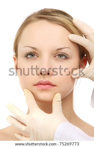 A surgeon's hands touching a female's face - stock photo