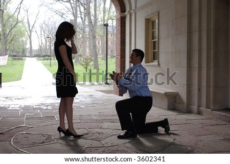 A surprise marriage proposal on a college campus - stock photo