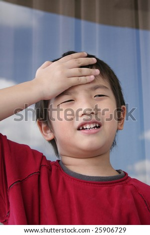 A surprised boy wearing red tee holding his forehead - stock photo