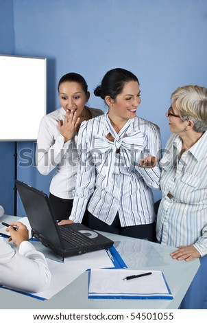 A surprised business young woman looking to laptop and the other two women laughing together ,they all having a meeting in a office