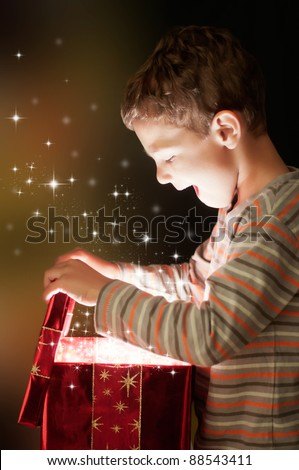 A surprised child opening and looking inside a magic gift - stock photo