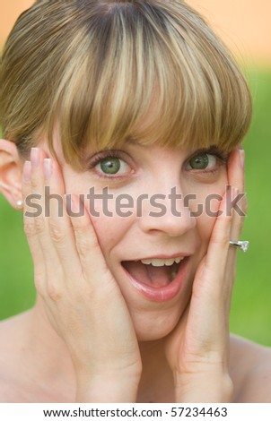 A surprised girl with an engagement ring on - stock photo
