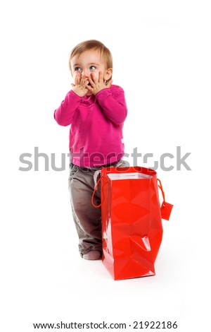a surprised little girl isolated on white background with a shopping bag - stock photo