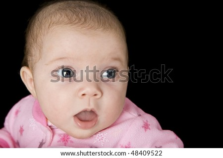 A surprised newborn baby girl on a black background with copy space