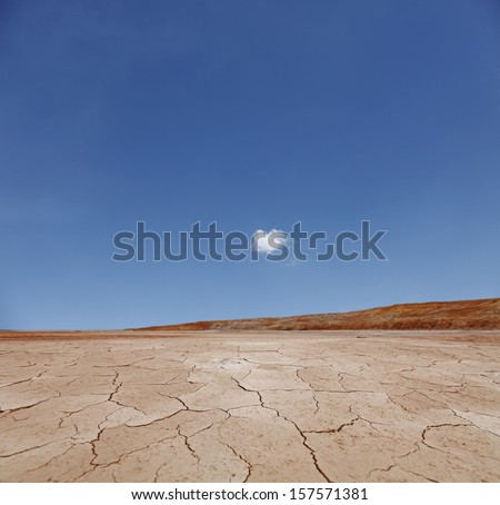 A surreal arid desert landscape with a blue cloudy sky.  - stock photo