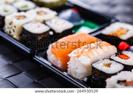 a sushi box or bento box with assorted sushi pieces over a dark black lunch mat - stock photo