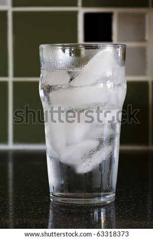 A sweating class of cold water with ice cubes sitting on granite counter in kitchen. - stock photo