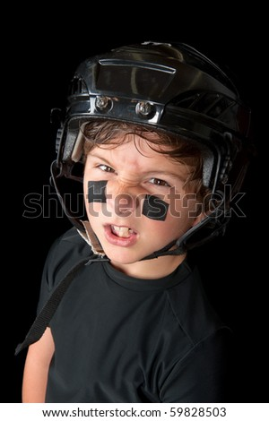 A sweaty youth hockey player wearing his safety helmet snarls at the camera. - stock photo
