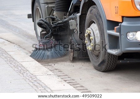 A sweeping machine cleans the street