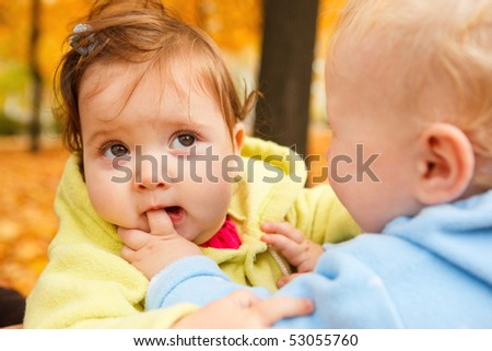 A sweet baby girl biting her friend's finger - stock photo