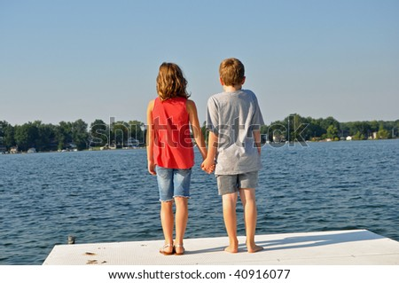 a sweet boy and girl hold hands while gazing out on the water - stock photo