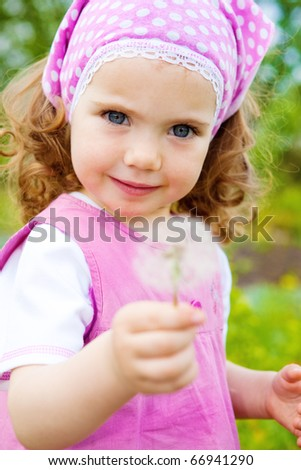 A sweet girl in the garden, with dandelion - stock photo