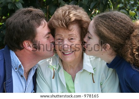 A sweet grandmother receiving kisses from her family. - stock photo