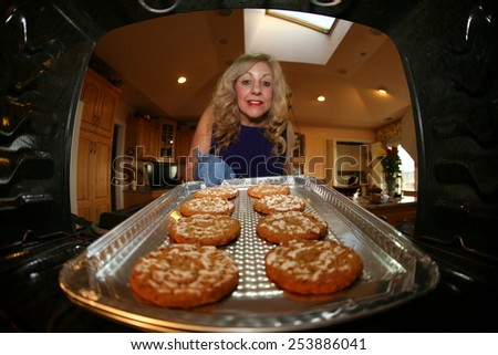 A sweet lady bakes up a batch of GLUTEN FREE Cookies. research showed between 0.5 and 1.0 percent of people in the US and UK are sensitive to gluten due to Celiac Disease. Gluten Free   - stock photo