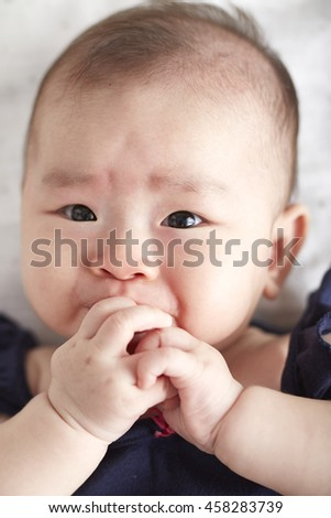 A sweet little baby girl in studio white background,eating hand