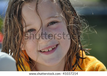 a sweet little girl drying off after swimming - stock photo