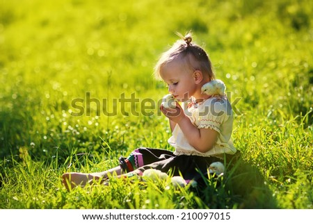 A sweet little girl sitting with chicks on the bright grass in a sunny summer day. Kids and nature  - stock photo