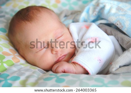 A sweet newborn baby girl is snuggled cozy in her nursing pillow, sleeping. - stock photo
