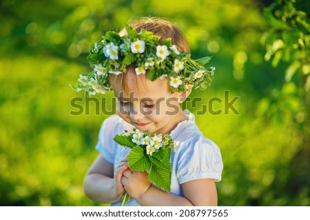 A sweet smiling little girl with a wreath of wild strawberry flowers in a white dress holding a twig of this plant in a green forest in a sunny summer day closeup