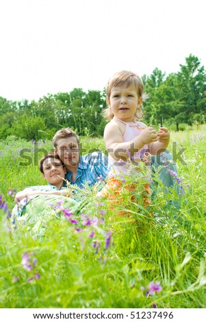 A sweet toddler standing in the meadow,  parents looking at her - stock photo