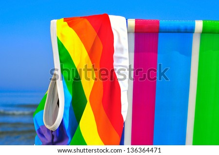 a swimsuit patterned with the rainbow flag on a deck chair of different colors on the beach - stock photo