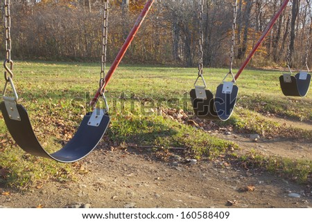 A swing set outdoors in a playground  - stock photo