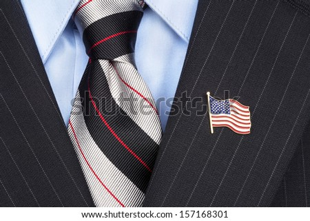 A symbolic American flag lapel pin on the collar of a businessman's suit - stock photo