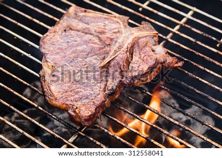 A t-bone steak frying on a grill, close up.