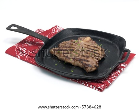 A T Bone steak in a frying pan  isolated against a white background - stock photo